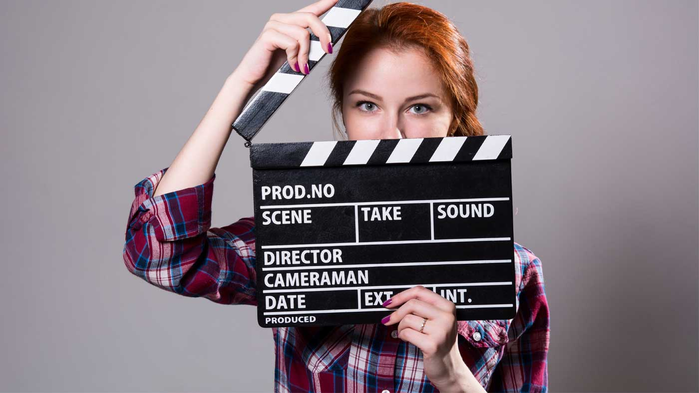 Girl holding clapperboard.
